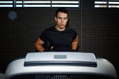 picture of treadmill  - Fit man running in a gym on a treadmill looking to the screen attractive sportsman at the gym doing exercise on the treadmill handsome brunette man at workout in gym running fast on a treadmill - JPG