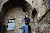 picture of gothic female  - Young female traveler searching right direction on city map beautiful tourist woman on vacation with a map in antique gothic city pretty young female tourist studying a map standing in gothic quarter - JPG