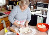 foto of grandma  - Senior woman or grandma preparing pie crust in her kitchen - JPG