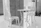 picture of metal sculpture  - white table and chair sculpturing rose tracery beside the pillar - JPG