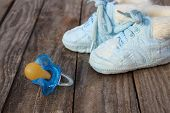 stock photo of pacifier  - baby shoes and a pacifier on the old wooden background - JPG