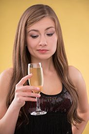 picture of sarcastic  - Portrait of  beautiful brown haired girl  holding an hand  glass  of champagne  looking  sarcastic at  it pulling her face - JPG