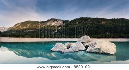 blue river with some huge rocks