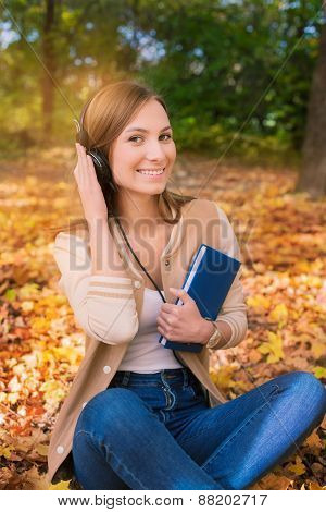 Student Sitting Among Maple Leaves, Listening To Headphones And Holding Book