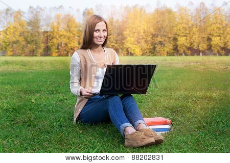 Student Sitting On Green Grass With Opened Notebook Lying On The Knees