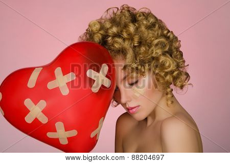 Balloon In Shape Of Heart And Hurt Young Woman