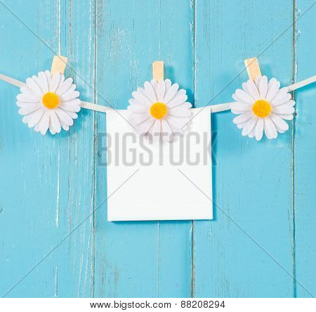 Chamomile flower clothespins with blank paper on blue wood background