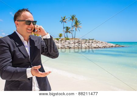 Businessman talking on phone at the beach