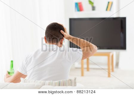 leisure, technology, mass media and people concept - man watching tv, drinking bottle beer and suffering from headache at home from back