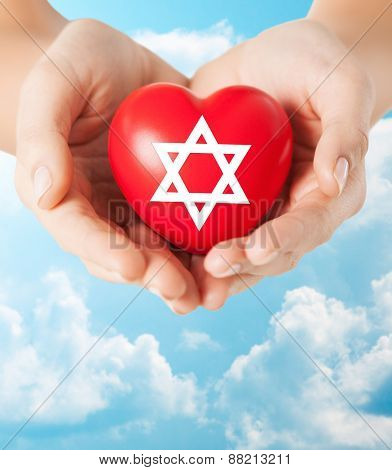 religion, christianity, jewish community and charity concept - close up of female hands holding red heart with star of david symbol over blue sky and clouds background