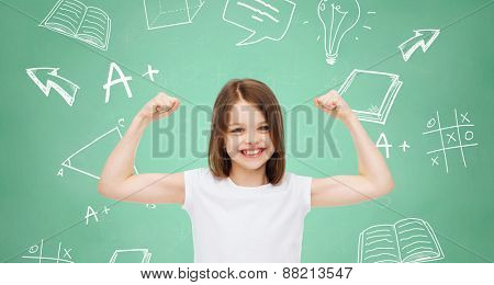 advertising, gesture, school, education and people - smiling little girl in white blank t-shirt with raised arms over green board with doodles background