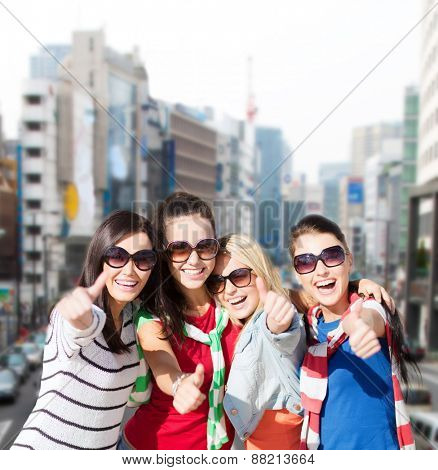summer holidays, vacation and people concept - happy teenage girls in sunglasses or young students showing thumbs up over city background