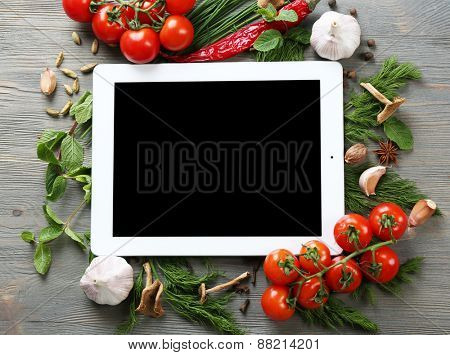 Digital tablet with fresh herbs, tomatoes and spices on wooden background