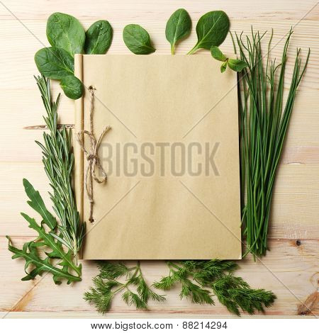 Open recipe book with fresh herbs on wooden background