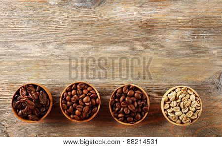 Coffee beans in small dishes on wooden background