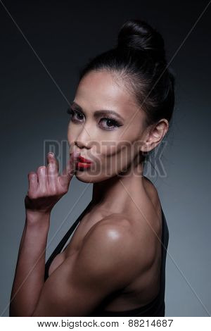 Close up Portrait of a Young Fit Woman in a Hushing Gesture While Looking at the Camera on a Gray Gradient Background.