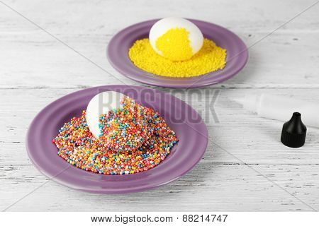 Decorating Easter eggs on color plate on wooden table, closeup