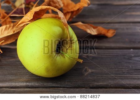 Apple with dried leaves on wooden background