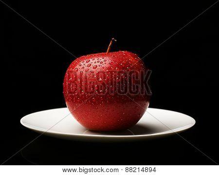Apple on saucer on black background