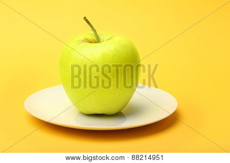 Apple on saucer on color background