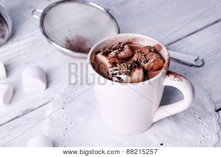 Cup of cocoa with marshmallows on wooden background