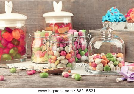 Multicolor candies in glass jars and cupcakes on wooden background