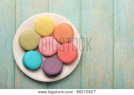 Tasty colorful macaroons in small plate on color wooden background