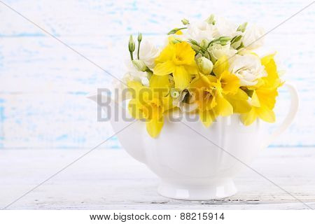 Beautiful bouquet of yellow daffodils and roses in teapot on wooden background
