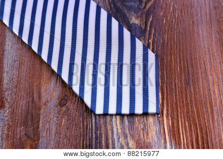 Striped necktie on wooden background