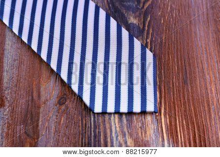 Striped necktie on wooden background