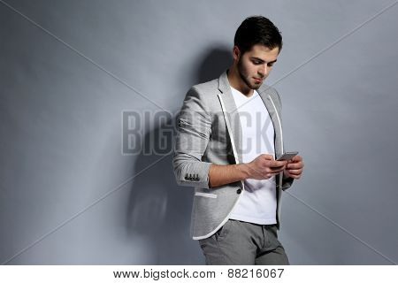 Young man with mobile phone on gray background