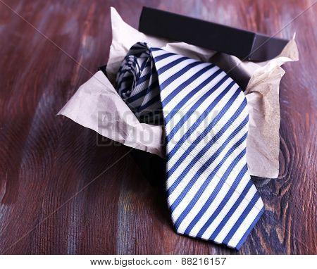 Striped necktie in box on wooden background