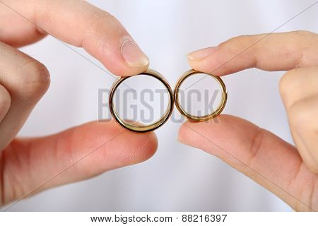 Woman and man holding wedding rings, close-up, on light background
