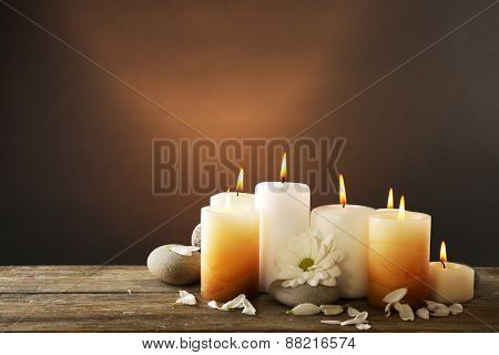 Candles with chrysanthemum on wooden background