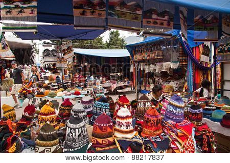 Colorful textile stall with hats in the popular Otavalo market, Ecuador