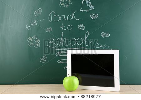 Digital tablet and apple on  desk in front of blackboard