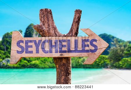 Seychelles wooden sign with beach background