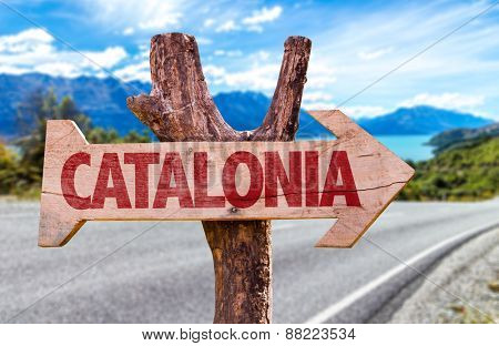 Catalonia wooden sign with road background