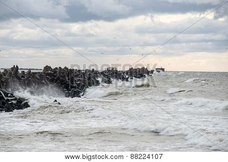 Waves Crushing Over Rocks In Sunset