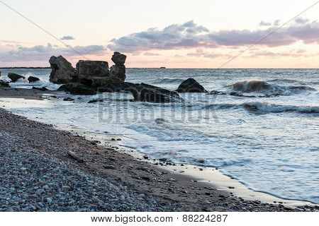 Waves Crashing Over Rocks In Sunset