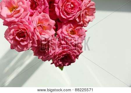 Bouquet of beautiful fresh roses on windowsill, closeup
