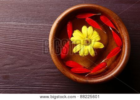 Flower petals in bowl, close-up, on wooden table background