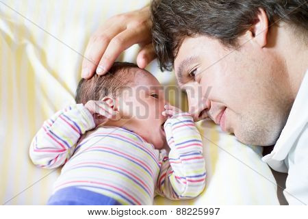 Young Father Hugging His Newborn Daughter