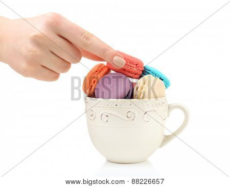 Female hand taking tasty colorful macaroons from cup isolated on white