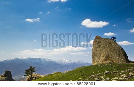 man climbing the cliff in mountains at above sea