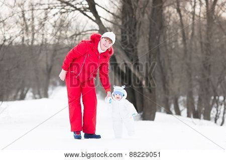 Active Beautiful Woman Walking With An Adorable Baby In A Snowy Park