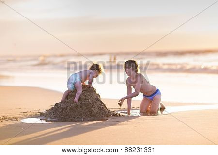 Cute Funny Baby Girl Climbing A Sand Castle Her Brother Was Building At A Beautiful Beach At Sunset