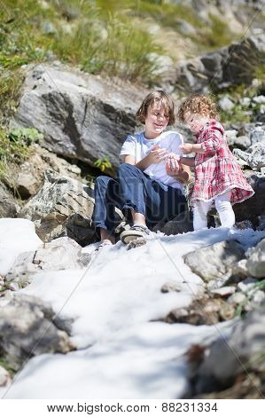 Happy Smiling Boy And His Little Baby Sister Playing With Snow In The Mountains