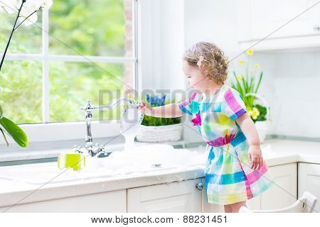 Cute Curly Toddler Girl In A Colorful Dress Washing Dishes, Cleaning With A Sponge