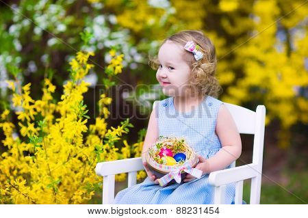 Cute Curly Toddler Girl In A Blue Dress Enjoying Egg Hunt In A Garden With Yellow Flowers
